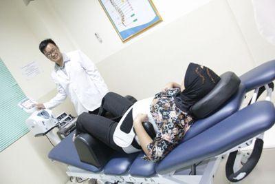 Penggunaan alat terapi dekompresi spinal